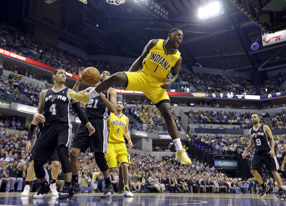 In this March 31, 2014, file photo, Indiana Pacers guard Lance Stephenson (1) reacts after a slam dunk over San Antonio Spurs guard Danny Green (4) and forward Tim Duncan (21) during the first half of an NBA basketball game in Indianapolis.