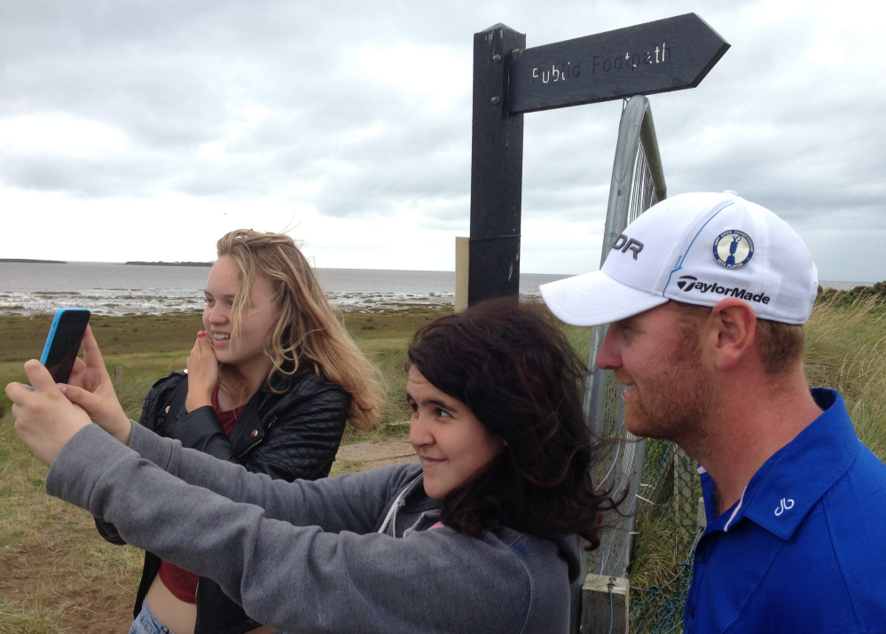 In this photo taken Wednesday with a mobile phone, spectators take a selfie with John Singleton of England at the Royal Liverpool golf club, where the British Open starts Thursday. Singleton, a 30-year-old factory worker, qualified for the Open on his first try.