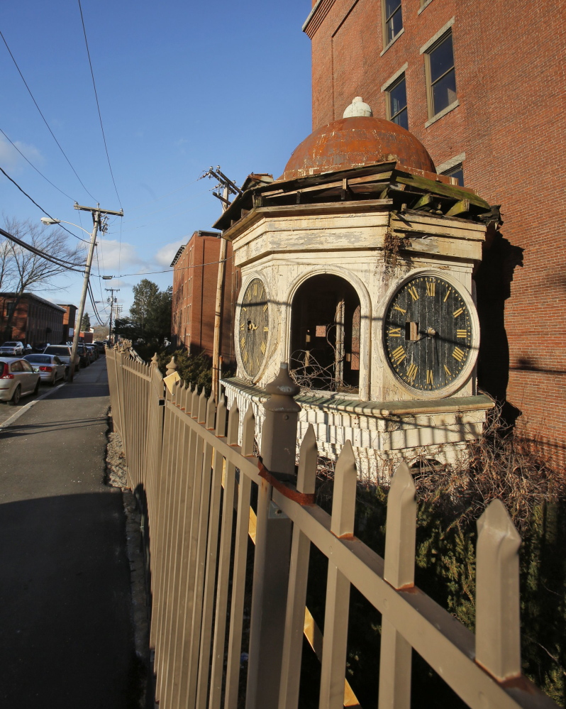 The clock tower rests on the ground near the deteriorating fence on Lincoln Street in Biddeford in this 2013 file photo.