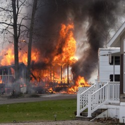 A fire started by sparks from a passing train blazes at Wagon Wheel RV Resort and Campground in Old Orchard Beach on May 8.