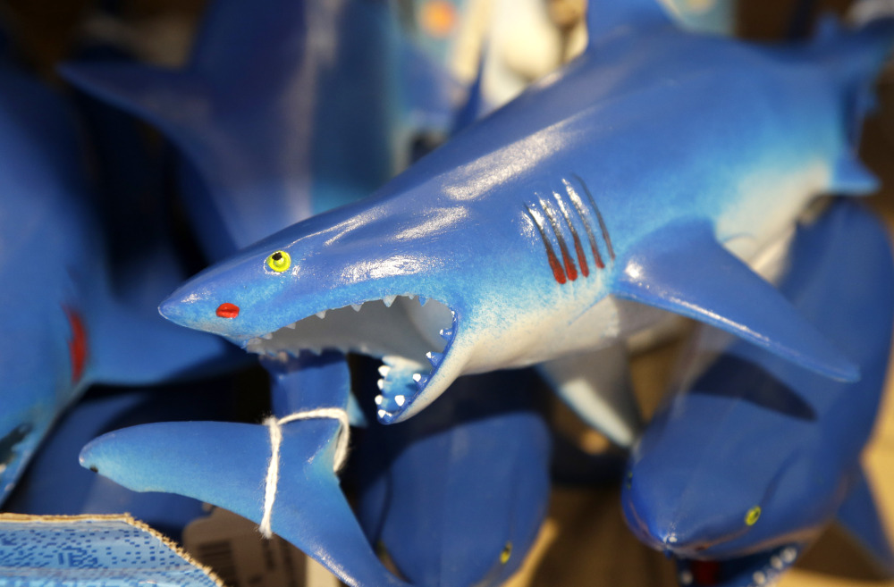 A bin is filled with plastic toy sharks in a souvenir shop in Chatham, Mass.