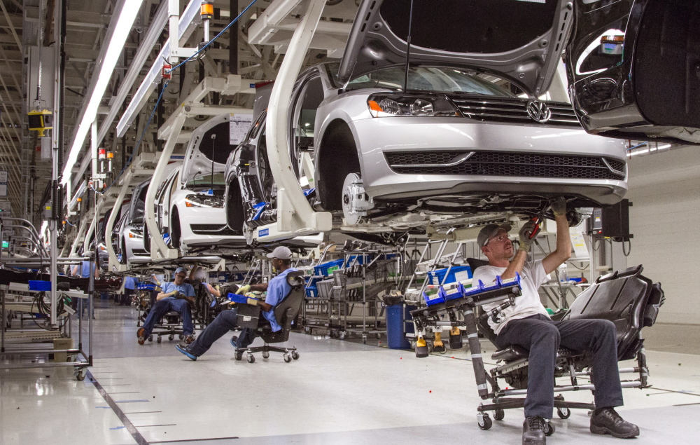 Employees at a Volkswagen plant in Tennessee assemble Passat sedans. Automakers including Volkswagen and GM are enticing Americans with ads promising cheap leases.