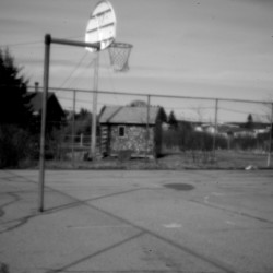 """A run-down basketball court at Pleasant Point. Decades after the land claims pact,, Maine's Passamaquoddy reservations have become uneasy places to thrive. Ira Gilbert, an unemployed tribal member at Indian Township, puts it succinctly: """"There's a big law problem here: There is none."""""""