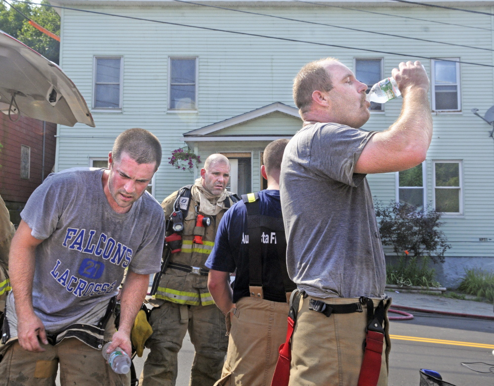 Firefighters pull off their gear and drink water Tuesday while battling a blaze in the attic of 32 State St. in Augusta.