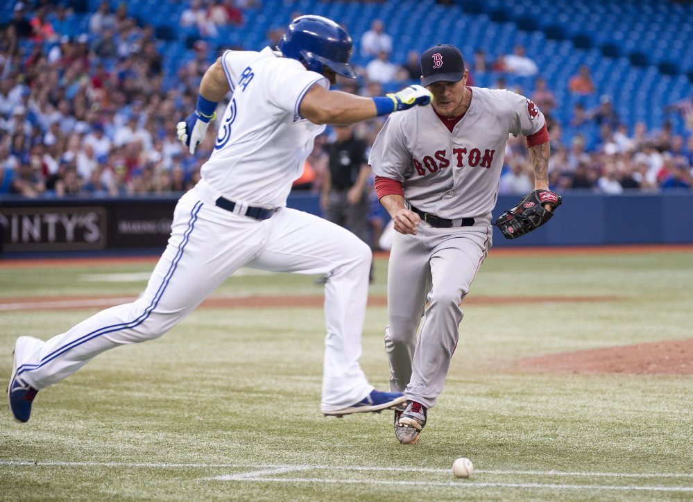 Toronto Blue Jays' Melky Cabrera, left, runs past Boston Red Sox starting pitcher Jake Peavy, beating a wild throw at first base, but was tagged out at second in a run down during the third inning Tuesday's game in Toronto.
