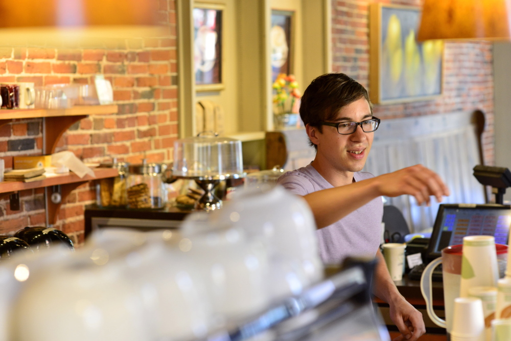"""Christopher McClure, 26, of Portland works as a barista Tuesday at Arabica Coffee, where he makes $10 an hour. He favors an increase in the city's minimum wage. """"For people in my situation ... I just don't see how they can get by,"""" he said."""