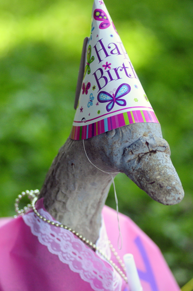 Staff photo by Joe Phelan Georgie the concrete goose statue is seen wearing birthday attire in the photo taken on Wednesday in front of Marjorie Scott's Eastern Avenue home in Augusta. She has been dressing it up for 20 years.