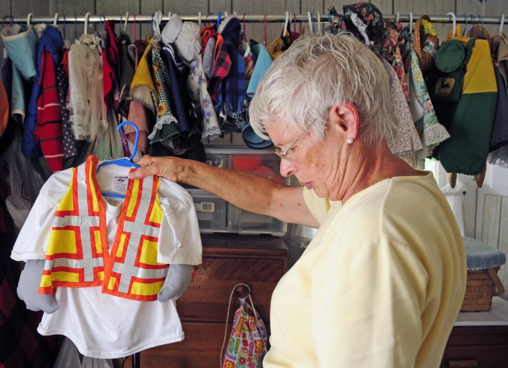 Staff photo by Joe Phelan Sally Kinkade hangs up one of the about 100 outfits that her mother Marjorie Scott has for the concrete goose on Wednesday in Augusta. Scott has been dressing up Georgie the Goose that stands in front her Eastern Avenue home for 20 years. This construction flagger outfit was made in honor of gas pipeline construction that was going on along Eastern Avenue last year.