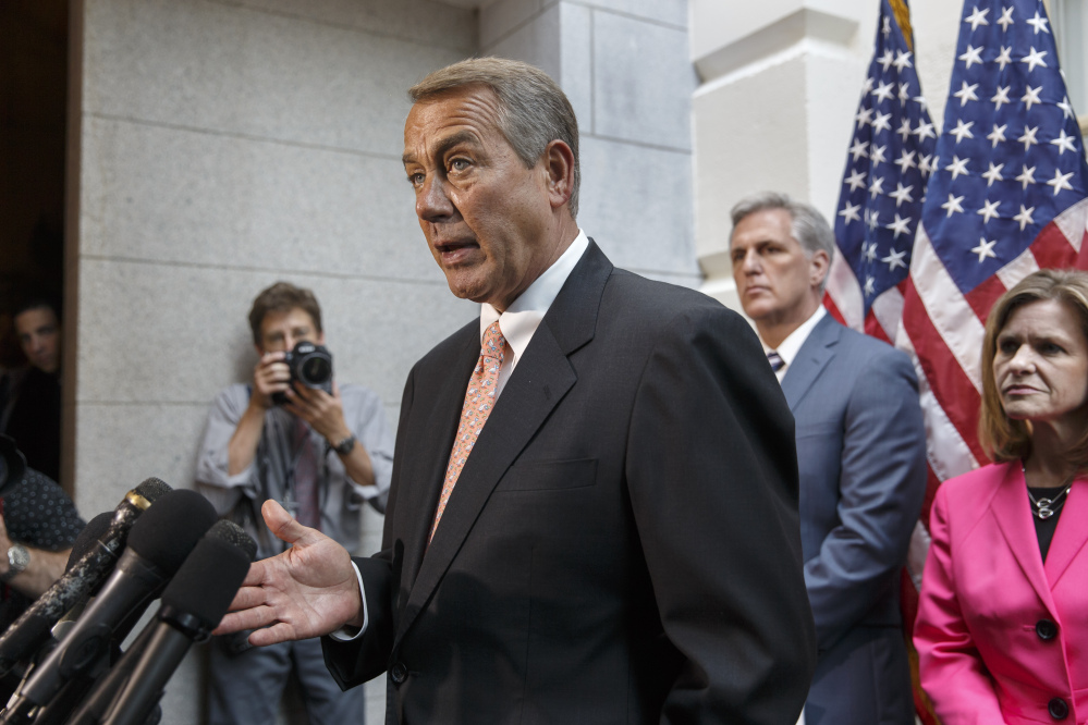 Speaker of the House John Boehner, R-Ohio, joined at right by incoming Majority Leader Rep. Kevin McCarthy, R-Calif., and Rep. Lynn Jenkins, R-Kan., talks with reporters  on Capitol Hill in Washington on Wednesday, following a Republican strategy session.