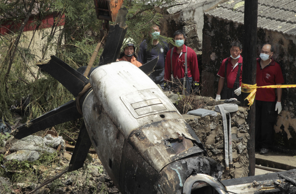 Emergency workers watch an engine lifted from the TransAsia Airways Flight GE222 crash site on the outlying Taiwan island of Penghu on Friday. Investigators were examining wreckage and flight data recorders for clues into a plane crash on the Taiwanese island that killed 48 people.