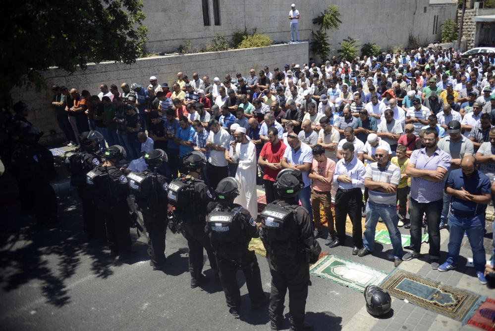 Israeli police officers stand in front of  Palestinian worshippers who were prevented from reaching the Al-Aqsa Mosque as they pray outside Jerusalem's Old City on Friday.