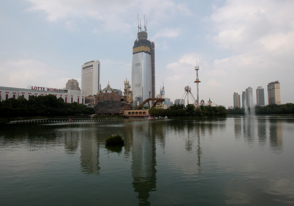 """The Lotte World Tower is under construction near Seokchon Lake in Seoul, South Korea, this month. Problems such as falling lake levels and sinkholes in residential neighborhoods have led to an official review of the project, reassessing an ethos of """"progress first, safety last"""" that was largely unquestioned as the country rapidly industrialized."""