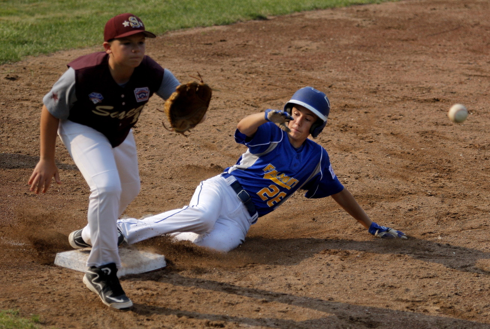 Saco's Luke Ham can't get the throw in time as Falmouth's Alex Smith slides safely into third base during the Little League state championship game in Biddeford on Friday. Gabe Souza/Staff Photographer