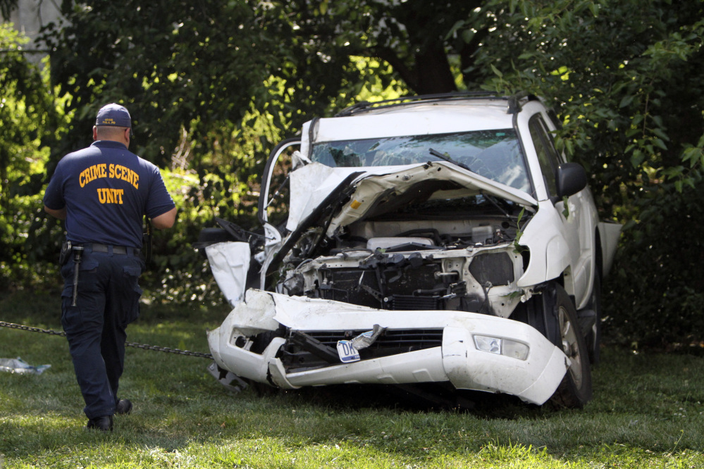 An investigator examines a heavily damaged SUV before it is towed from the scene of a fatal accident in North Philadelphia.
