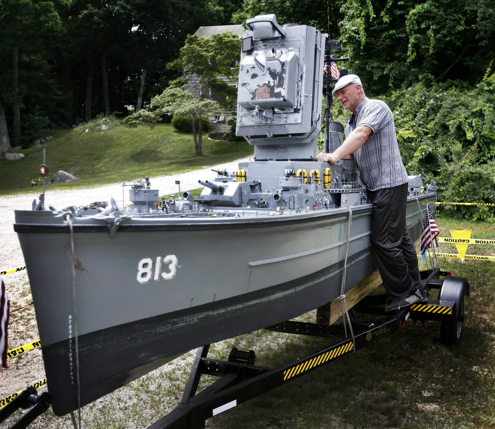 Steve MacDonald of Hingham poses with his 20-foot-long model of World War II battleship USS Charles Dean in Cohasset, Mass. MacDonald is selling the intricate replica for $10,000. The boat can be taken out on water.