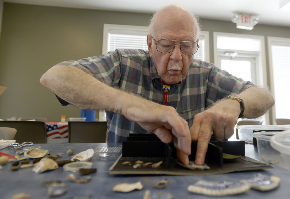 Volunteer Theodore Davi prepares a display with items excavated over the last eight years from the Avery hive site in Groton, Conn. The Associated Press/Tim Martin, The Day