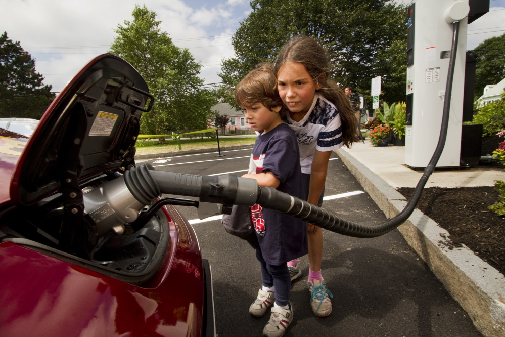 Luis Frederick Robinson, 4, and his sister Kerry-Elizabeth, 8, watch an electric car get quick-charged at a charging station that opened at the South Portland Community Center last week. Installing more chargers eases motorists' concerns that their battery will run down and leave them stranded.