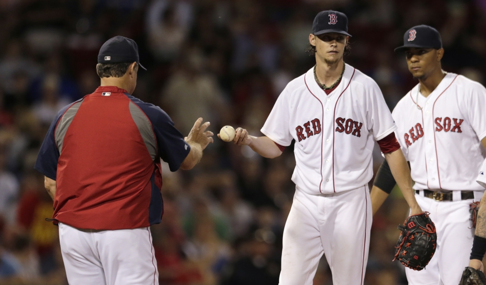 Red Sox starting pitcher Clay Buchholz hands the ball to manager John Farrell as he is taken out of Monday's game against the Toronto Blue Jays in the sixth inning. Buchholz gave up seven runs, all earned, on seven hits.