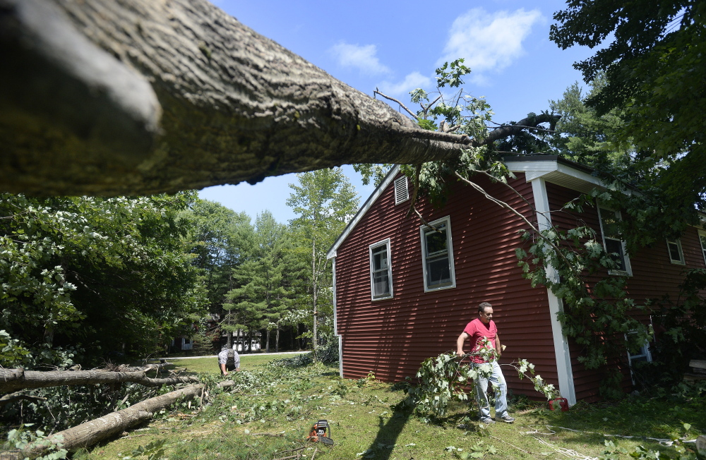 Dave Vastille of Saco cleans up debris Tuesday at the Limington home of his nephew Josh St. Pierre. Meteorologists with the National Weather Service confirmed Tuesday that a tornado touched down on Monday afternoon in the area southwest of Sebago Lake.