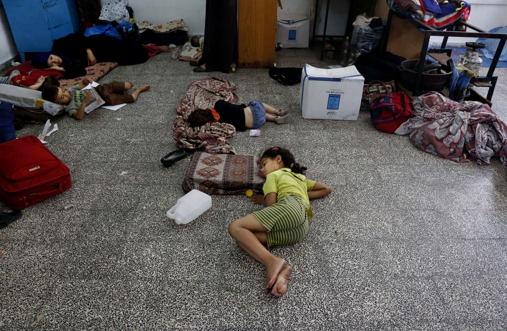 Palestinian children lay on the floor at the Abu Hussein U.N. school, hit by an Israeli strike earlier, in the Jebaliya refugee camp, northern Gaza Strip, Wednesday. Israeli tank shells slammed into a crowded U.N. school sheltering Gazans displaced by fighting on Wednesday, killing more than a dozen and wounding tens after tearing through the walls of two classrooms, a spokesman for a U.N. aid agency and a health official said.