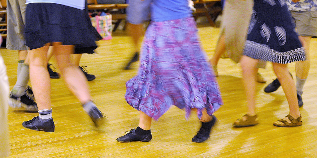 Dresses blur as they slip by in a square dance.