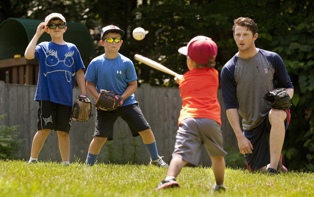 Cal Hodgdon, 7, and Camden Charron, 9, wait to field the ball while playing with 4-year-old Jackson Charron and McCarthy in the Charron family's Falmouth yard.
