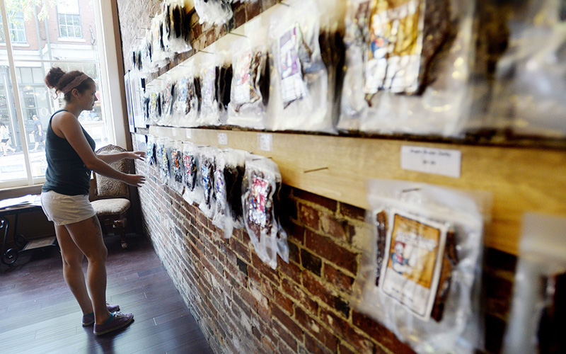Alanah Meeks assistant manager of the Old Port House of Jerky stocks the display wall with jerky Thursday. Shawn Patrick Ouellette/Staff Photographer