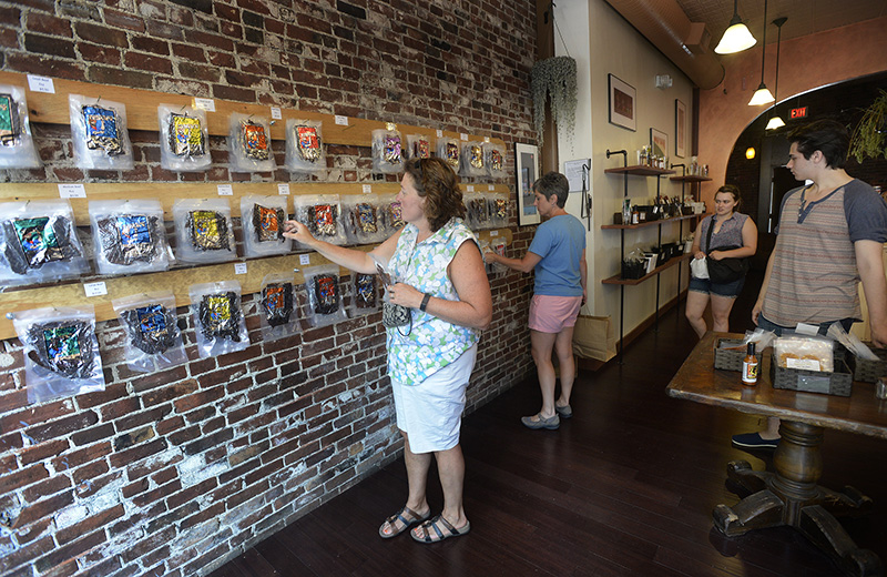 Customers look over the variety of jerky at the Old Port House of Jerky Thursday. Shawn Patrick Ouellette/Staff Photographer