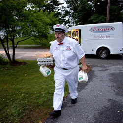 With his 1961 Chevrolet milk truck sitting in the background, Jim Pastor makes his way up a driveway in Saco, two gallons of milk and two dozen eggs in hand, just one of the many dozen stops he makes along his delivery route in the Biddeford/Saco area.