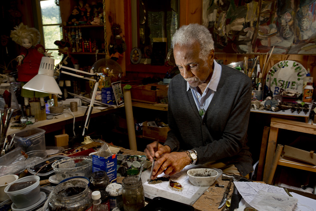 Artist Ashley Bryan, 91, demonstrates how he works with sea glass to make art at his workshop on Little Cranberry Island. Bryan has visited the island to create art since 1946 and retired there in the 1980s.