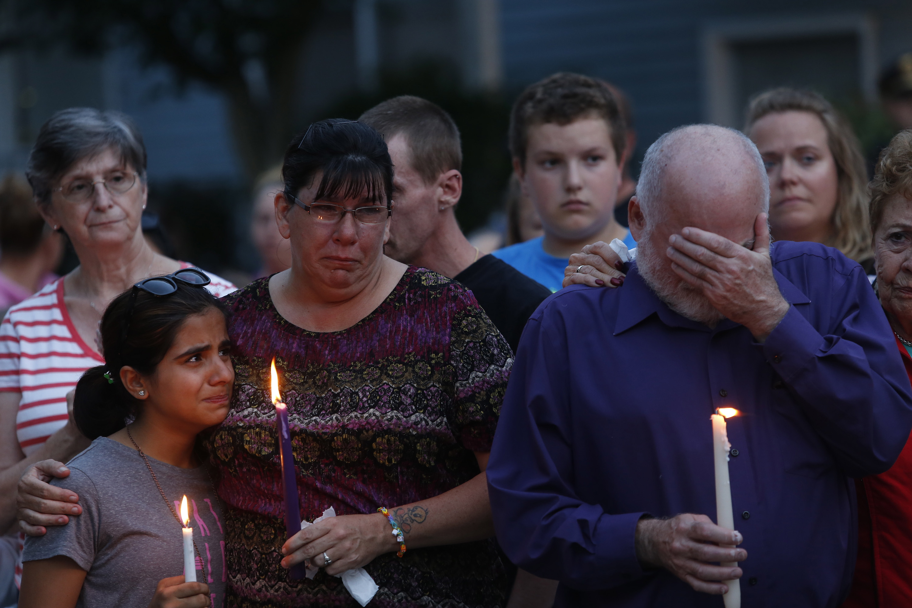 """Becca Garland comforts her neighbor Youna Karim, 12, during a vigil for the Smith family at the RiverView apartments in Saco on Tuesday night, while Joel Smith's father, Steve Smith, covers his face.  Garland said, """"I was her best friend here,"""" speaking of Heather Smith, one of the victims. """"We had a barbeque on Saturday night and I kissed her and told her 'I love you and I will see you tomorrow.'"""""""