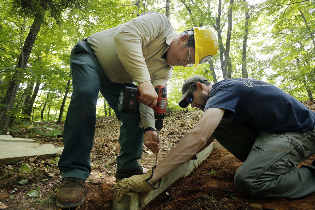 Kenway, left, and Tom Cavanaugh work on the privy on a section of the trail in Caratunk.