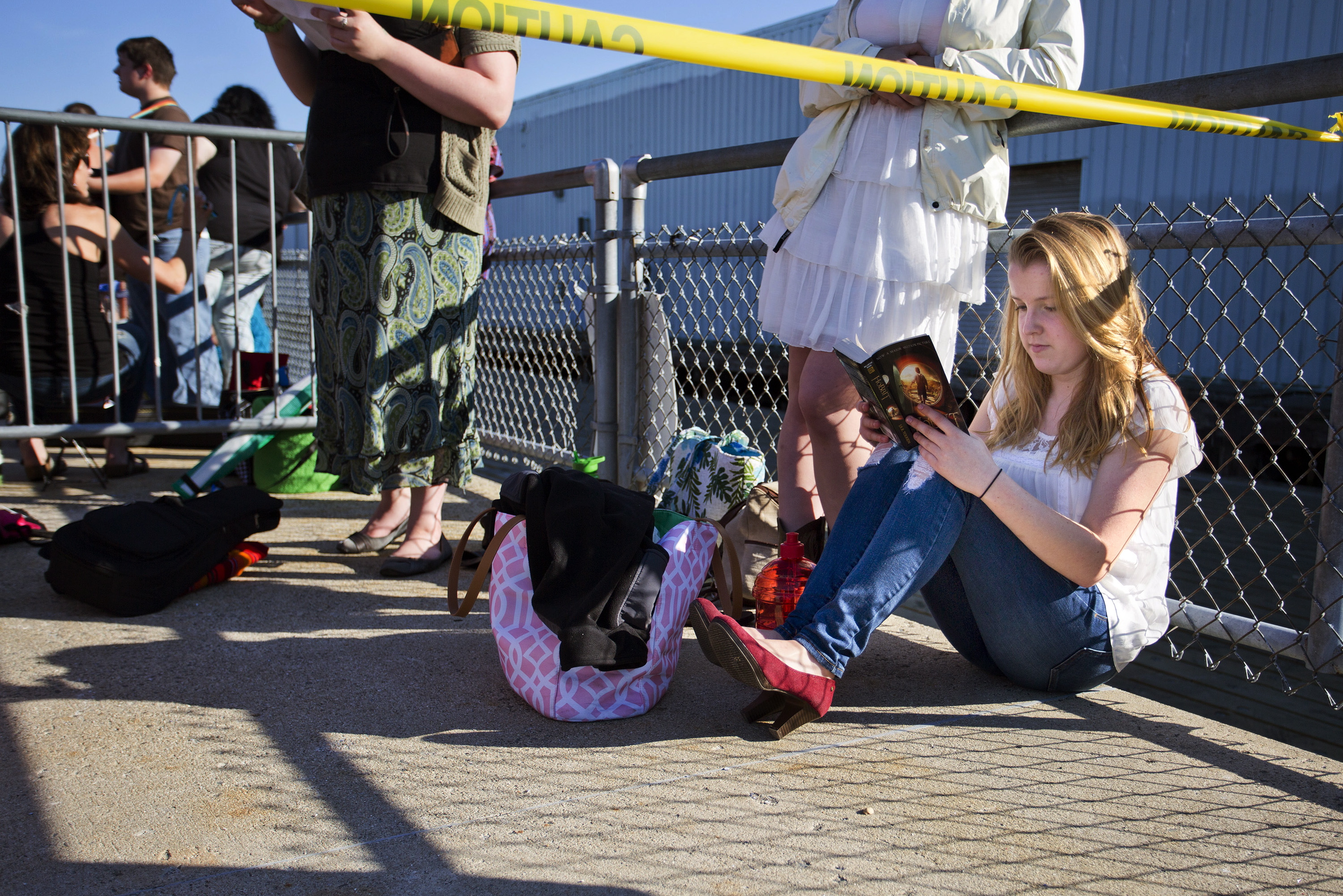 """Abigail Day, 17, of Cornish, reads a book while waiting to audition for """"American Idol"""" at the Maine State Pier on Wednesday. Day, who planned to sing """"I See Fire"""" by Ed Sheeran, was in line at 2 a.m."""