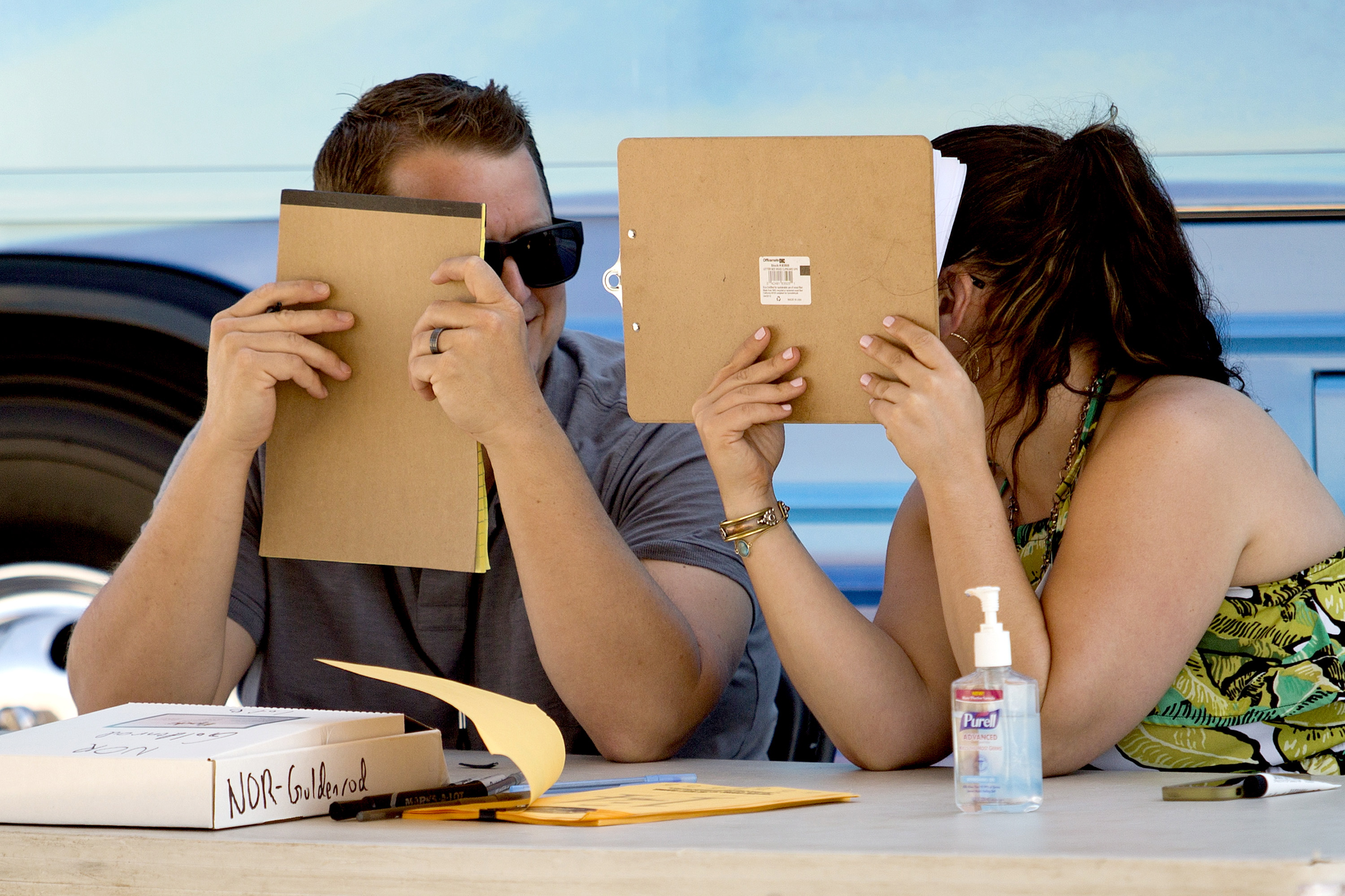 """Brian Robinson, a senior producer with """"American Idol,"""" and Nancy Yearing of 19 Entertainment, converse behind clipboards and notepads as they talk about whether or not a person who auditioned for the show made the first cut at the Maine State Pier on Wednesday."""