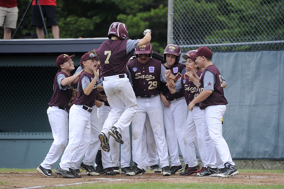 The Saco Little League team celebrates Calvin Christoford's homerun at the Hill Street Field on Thursday. Logan Werlinger/Staff Photographer