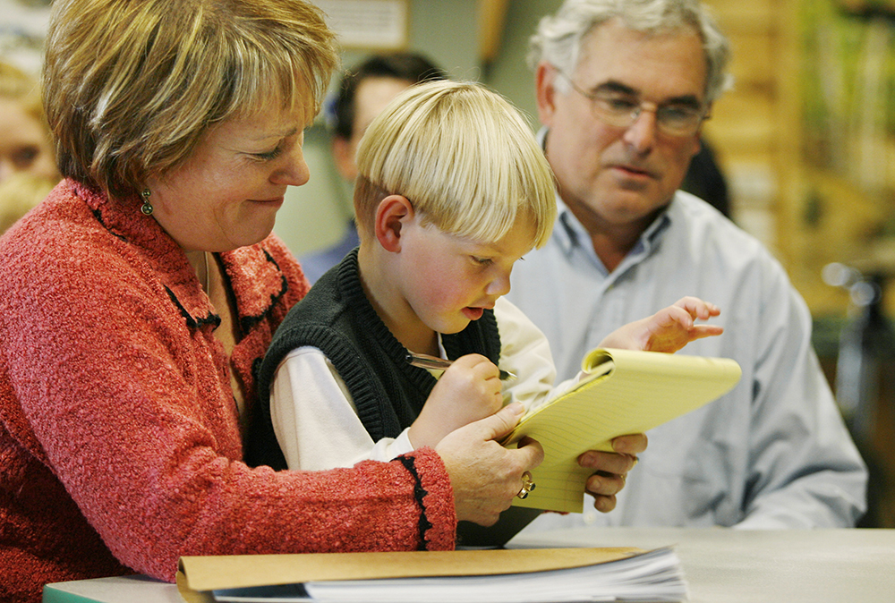 """Jane Riseman and husband Walter look on as their foster child, Michael William Riseman, draws before the start of the adoption ceremony in Portland in 2005. The Risemans adopted Michael, who had been known as """"Baby Jason"""" when he was found near death in a Portland motel. Michael was a month old when his parents were arrested in April 2002 at a Motel 6 in Portland. Police say the father, Jason Hann, confessed to killing two other children, a daughter in California and his son in Vermont."""