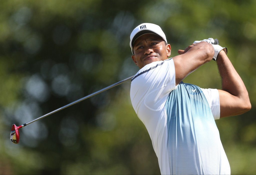 Tiger Woods plays a shot off the eighth tee Thursday during the first round of the British Open, Woods' first major tournament of this year. Woods finished with a 69, three strokes off the lead.
