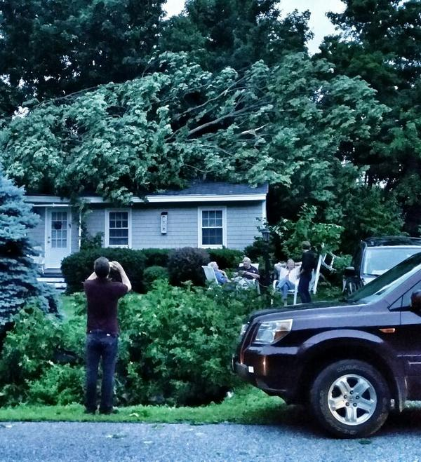 Residents wait outside a house in York that was hit by a falling tree during Tuesday's storm.