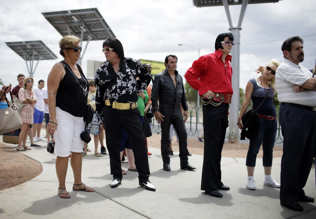 """Elvis tribute artists participating in the Las Vegas Elvis Festival wait in line to take pictures in front of the """"Welcome to Las Vegas"""" sign in Las Vegas. Several of the tribute artists took a bus tour around Las Vegas during the convention."""