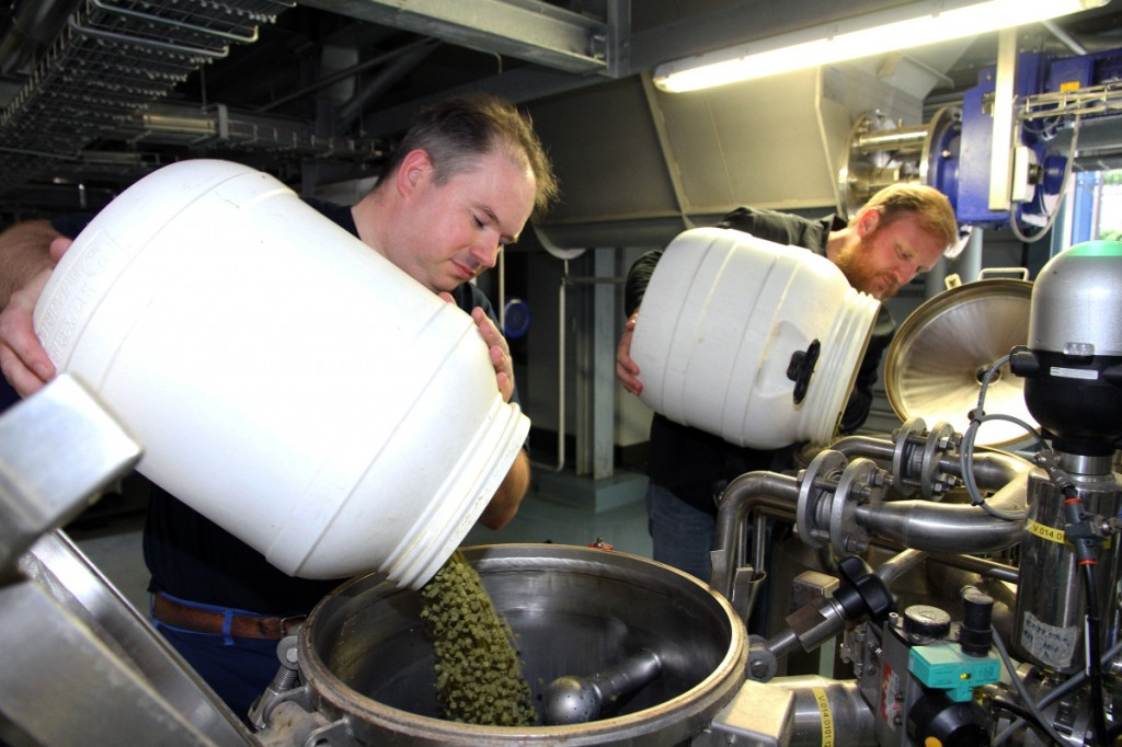 Alexis Briol, of Brasserie St-Feuillien in Belgium, left, and Green Flash brewmaster Chuck Silva, pour hop pellets into a batch of beer. San Diego-based Green Flash is making and selling fresh beer in the European market under a handshake deal with Brasserie St-Feuillien.