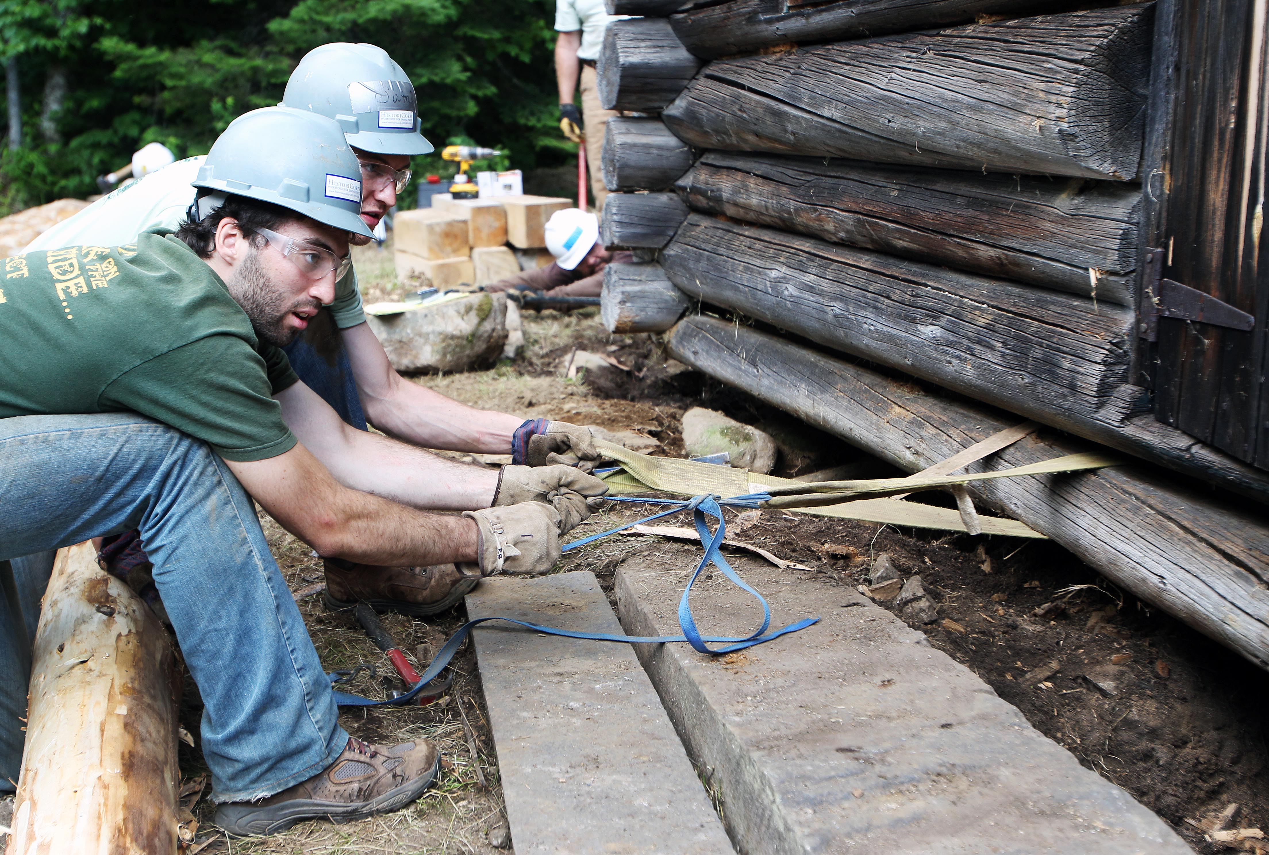 Volunteers Alex Gunn, front, and Andrew Griesemer work to pull out a beam on the Fabyan Guard Station in New Hampshire White Mountain National Forest in Carroll, N.H., on July 10.