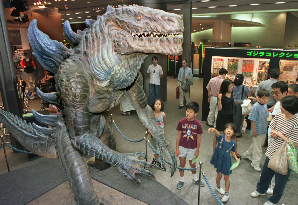 Children look at a 9-foot model of a 1998 Godzilla character in a Tokyo auto showroom.