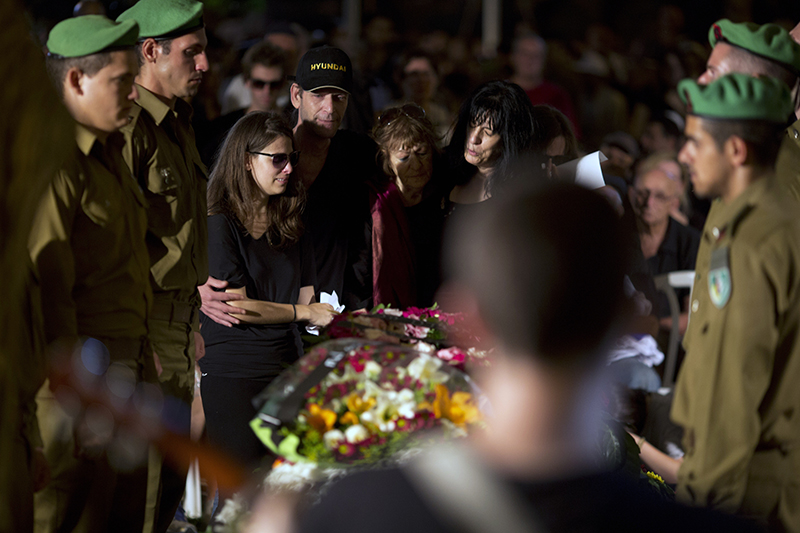 The family of 2nd Lt. Roy Peles, an infantry officer, mourns during his funeral at Kiryat Shaul military cemetery in Tel Aviv, Israel, Sunday. The Associated Press