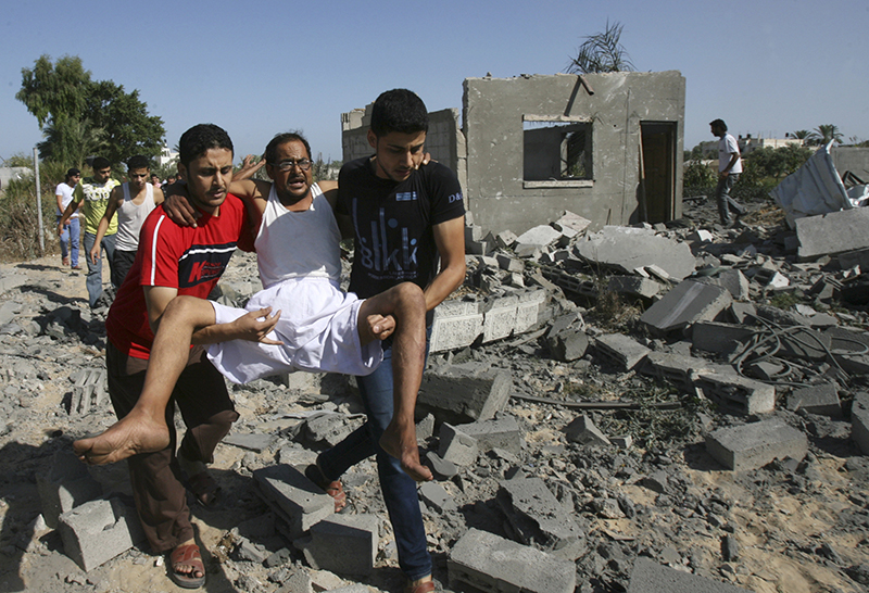 Palestinians help a man wounded as they walk over the rubble of destroyed buildings following an Israeli airstrike in Khan Younis in the southern Gaza Strip, Wednesday. The Associated Press