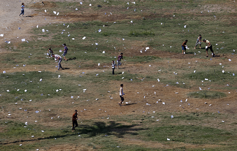 Palestinians gather leaflets that fell from an Israeli plane warning residents in Gaza City, Wednesday. The Associated Press