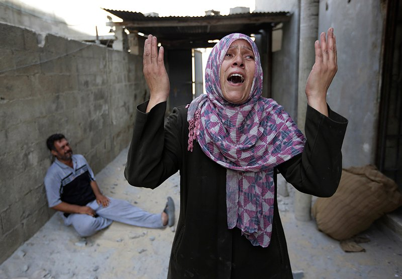 As her brother-in-law Mazen Keferna, background left, weeps, Palestinian Manal Keferna, 30, right, cries upon her return to the family house, destroyed by Israeli strikes in Beit Hanoun, northern Gaza Strip, Saturday. The Associated Press