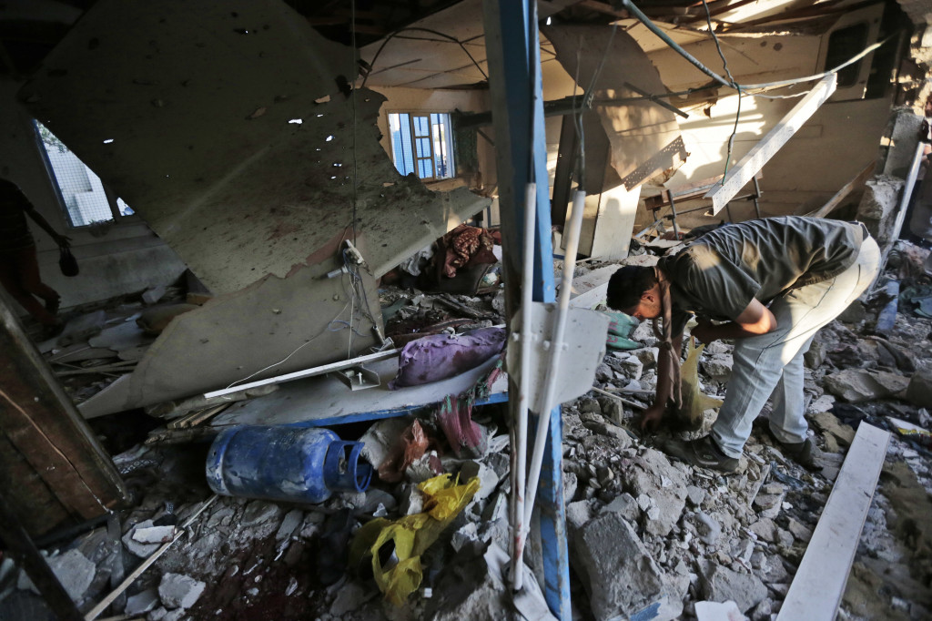 Palestinians sift through debris in a classroom at the Abu Hussein U.N. school in Jebaliya refugee camp, northern Gaza Strip after it was hit by an Israeli tank shell on Wednesday. The Associated Press