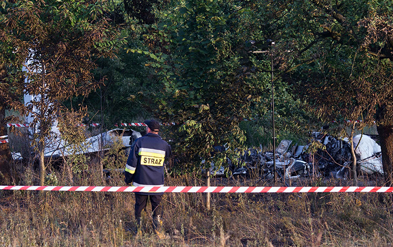 A firefighter officer examines the crash site of a plane near the village of Topolow in Poland, Saturday. The Associated Press