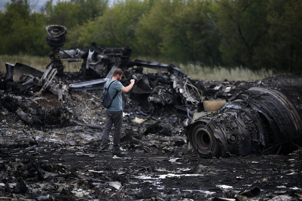 A journalist takes photographs at the site of Thursday's Malaysia Airlines Boeing 777 plane crash near the settlement of Grabovo.