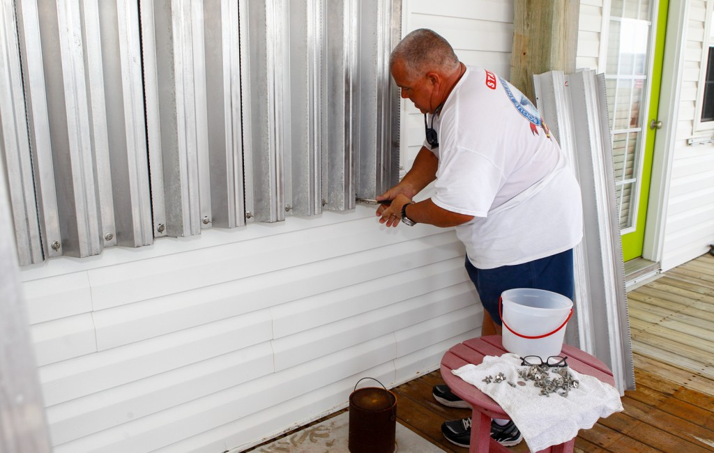 Mike Stanley, owner of Bougue Inlet Fishing Pier in Emerald Isle, N.C., installs shutters over the windows of his rental properties before the arrival of Hurricane Arthur, Thursday.  The Associated Press